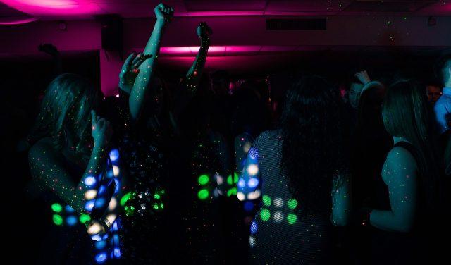 Darkly lit bar full of dancing women