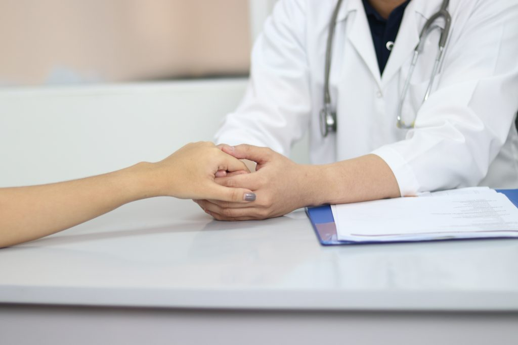 A doctor holds a patient's hand