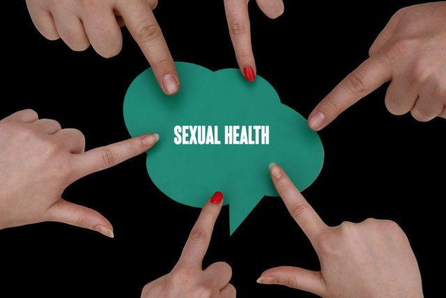 "Sexual Health, Health Concept. The words ""sexual health"" in white on a green thought bubble against a black background surrounded by pointing fingers."