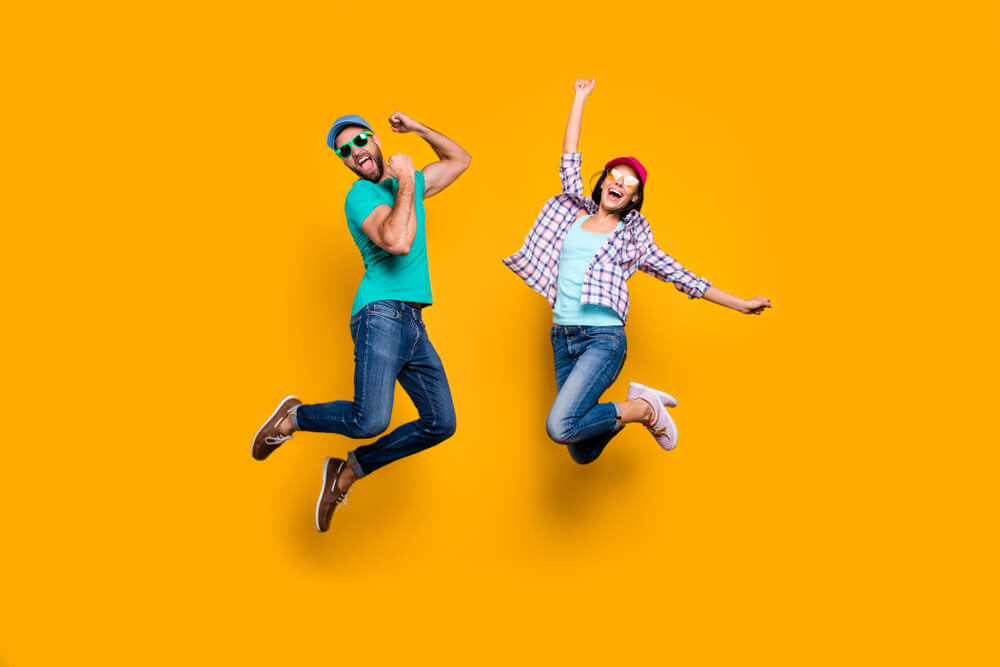 Portrait of funky active couple jumping with raised fists celebrating victory wearing casual clothes isolated on vivid yellow background; enthusiastic consent concept