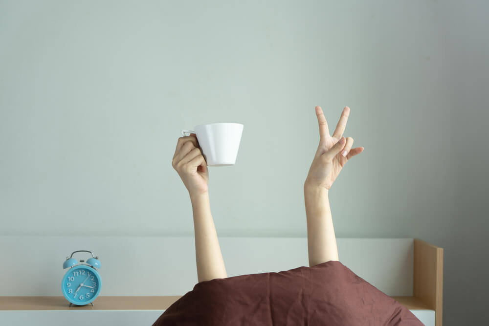 Woman showing funny v sign holding blue tea cup relaxing in bed room, Young woman with two hands drinking coffee in blue cup after awaking. consent is like tea analogy concept.